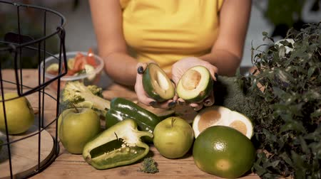 dividindo : Woman dividing an avocado in half at the wooden table full of healthy nutritious food, closeup