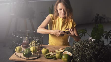домохозяйка : Smiling girl taking photo of healthy food, indoor shot Стоковые видеозаписи