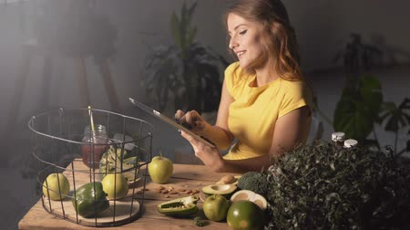avocado : Joyful girl typing a recipe on a tablet at the kitchen table full of fresh green vegetables and fruits Stock Footage