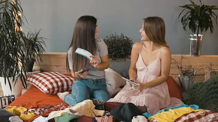 timeout : Joyful caucasian girls reading information on tickets on comfortable red bed Stock Footage