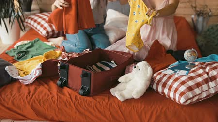 timeout : Girlfriends packing red suitcase, indoor shot in cozy bedroom Stock Footage
