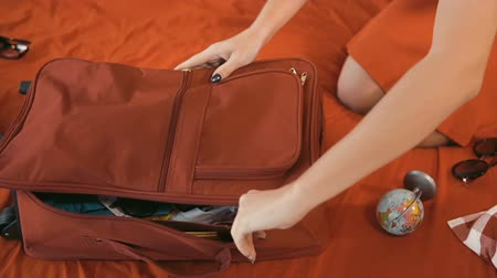 timeout : Girl finishes packing red travelling bag and puts the globe on it, indoor shot on large red bed