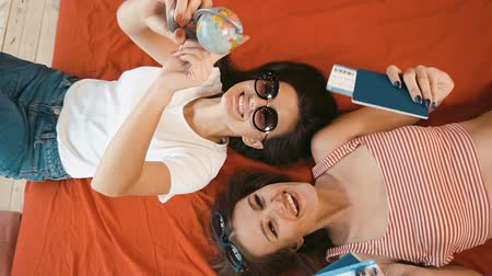 timeout : Happy slim girls dreaming about holidays with passports, tickets and globe in hands while lying on the bed Stock Footage