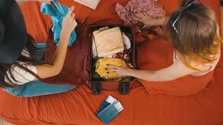 pas : Attractive caucasian girls packing traveling bag on large persian red bed