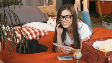 футболки : Beautiful long-haired girl in glasses chatting on the phone about upcoming trip, indoor shot in cozy bedroom