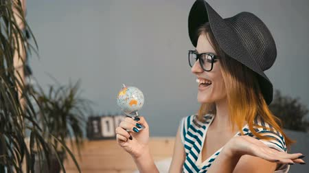 timeout : Beautiful girl in black elegant hat picking up a country on the globe, indoor shot Stock Footage
