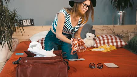 pas : Busy girl in beach black sunhat packing the dark red suitcase on big bed