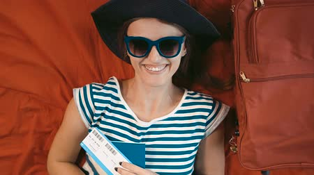 voyager : Relaxed and happy traveller with ticket and passport lying on persian red bed next to the suitcase