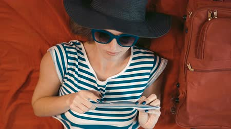 voyager : Joyful female traveller in striped t-shirt reading the ticket on big persian red bed