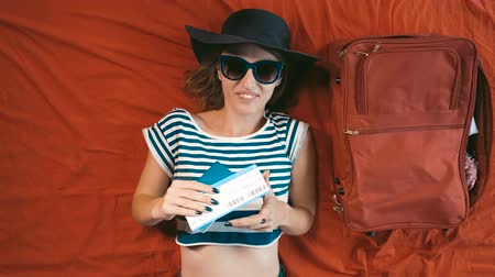 voyager : Happy caucasian girl in beach hat and fashionable sunglasses lying on the bed while holding passport and ticket