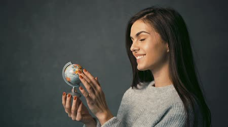 voyager : Beautiful long-haired girl taking a view of countries on the globe happily, isolated shot Stock Footage