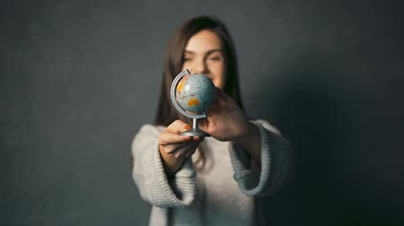 voyager : Beautiful dark-haired girl in warm grey sweater turning the globe, indoor isolated shot
