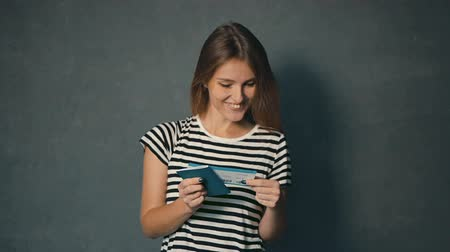 voyager : Smiling girl in striped t-shirt reading information on ticket, isolated shot in the grey background Stock Footage