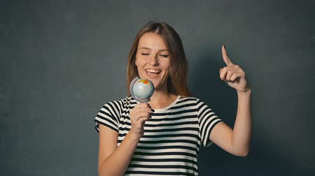 timeout : Female tourist in striped t-shirt playing happily with the globe, indoor shot Stock Footage