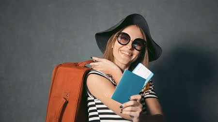 voyager : Smiling traveller with suitcase at the back showing passport and ticket, isolated shot Stock Footage