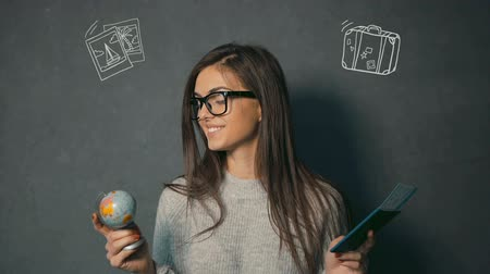 voyager : Smiling brunette in glasses looking at globe and passport with the ticket in the grey background with travel animation icons