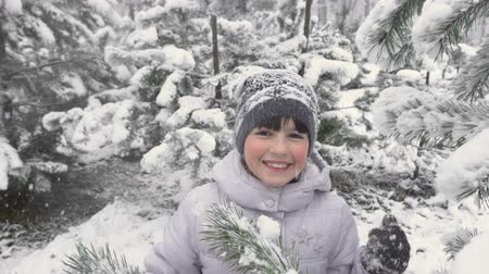 snow caps : Cute young girl smiling before snowy tree in winter time