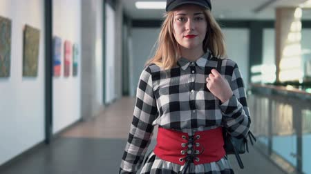 типы : Young stylish woman wears black hat walks with bag on her shoulder in modern building, indoor slowmotion