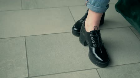 cipőfűző : Woman walks wears black leather stylish fashionable boots and holds bag, indoor slowmotion