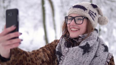 snow caps : Attractive girl wears glasses have videochat by smartphone in winter snowy park Stock Footage
