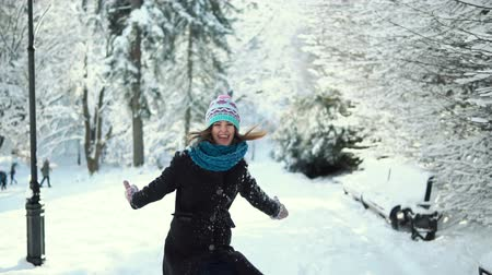 knitted gloves : Young happy girl having fun in the winter park, outdoor sunny day slowmotion