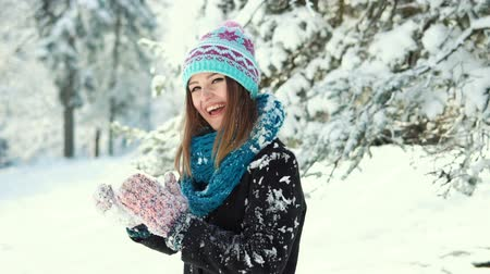 knitted : Young happy girl playing snowballs in the winter park, outdoor sunny day slowmotion