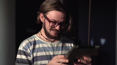 wąsy : Smiling teenager in glasses using tablet, standing in a dark room near the window, indoor shot in the sunlight Wideo