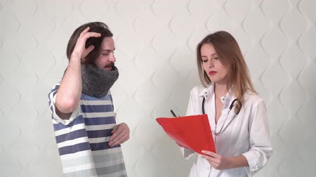 консультация : Intelligent young doctor with red folder asking questions about illness, patient - handsome boy with a moustache in warm gray scarf Стоковые видеозаписи