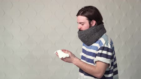 coughing : Dark-haired caucasian boy coughing and blowing his nose into a tissue, indoor shot of a sick boy in gray scarf and striped t-shirt