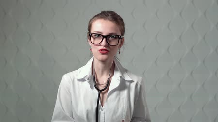 medical student : Pretty fair-haired doctor with stethoscope giving a talk, wearing white doctors smock and glasses, isolated shot Stock Footage