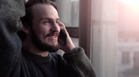 bigode : Smiling man with a beard and moustache having a pleasant talk on the phone, indoor shot near window in the daylight