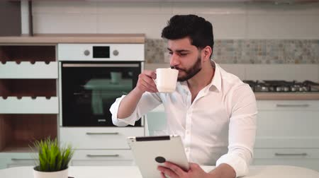 microonda : Handsome bearded man with back wavy hair using tablet while having coffee in modern, spacious kitchen, wearing elegant white shirt, looking out for the spouse happily at the table