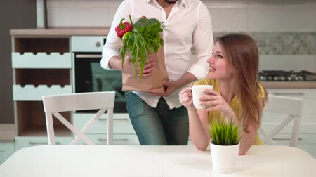 uzun ömürlü : Lovely long-haired woman having tea in cozy white kitchen, good-looking tall man bringing shopping bag with healthy, nutritious food, young family couple having a pleasant talk in warm home atmosphere