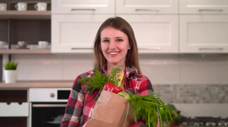 paprika : Tall and slim woman, in stylish checked shirt, brings home shopping pack with healthy, organic food, indoor shot in light kitchen