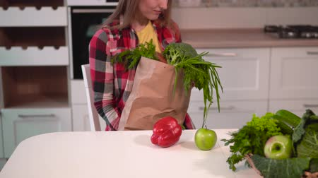 uzun ömürlü : Young caucasian woman, in checked shirt and yellow t-shirt, unpacking shopping bag, taking out apple, pepper, broccoli, parsley, carrot and putting them next to basket with fresh, healthy food
