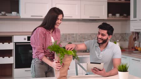 パック : Attractive young wife brings shopping pack with green food home, handsome smiling husband trying lettuce immediately from the pack while holding metallic tablet