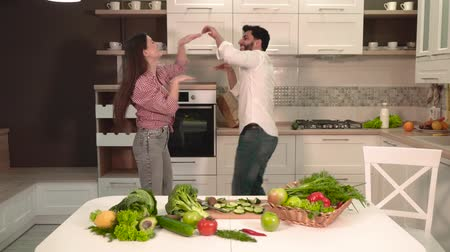 microonda : Happy family couple dancing in the light spacious kitchen, indoor shot behind the table full of fresh, nutritious vegetables and fruit