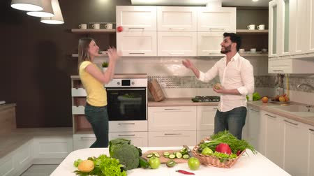 microonda : Young family couple having fun, dancing and singing in the light spacious kitchen, holding apple and tomato in hands, indoor shot behind the table with fresh, nutritious vegetables and fruit Stock Footage