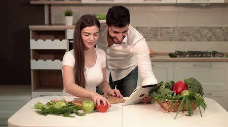 microonda : Great family evening, pretty dark-haired woman cutting tomato, handsome tall man showing pictures on tablet, indoor shot in fine white kitchen, concept of healthy eating and beautiful body