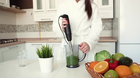avocado : Cheerful girl in white bathrobe making smoozie in blender, breakfast time at the table with healthy food, indoor shot in a modern white kitchen Stock Footage