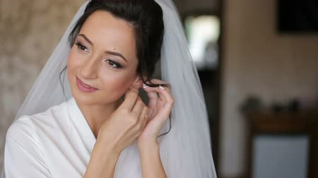 güzel : Brunette bride wears white robe and veil sets earrings in the room
