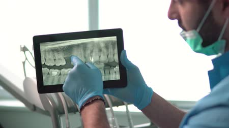 dava : Intelligent dentist showing teeth x-ray on tablet, well-built man in green mask and blue gloves explaining particular case, sitting before dental chair in light huge office Stok Video