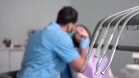 equipped : Focused dentist talking to joyful patient during teeth check up, defocused indoor shot from dental chair unit Stock Footage