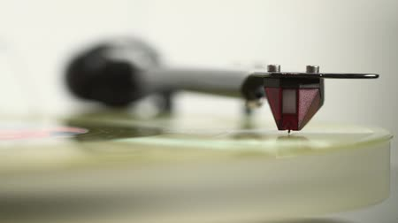 tonearm : Close up of vinyl disc on the player, woman hands set needle head