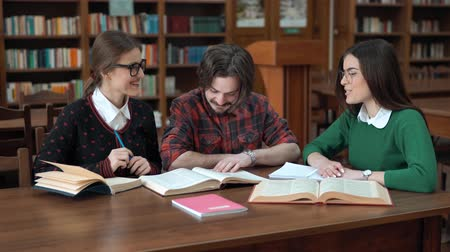 livros didáticos : Smiling groupmates talking about read information, picking up necessary details for home assignment, indoor shot in cozy college library