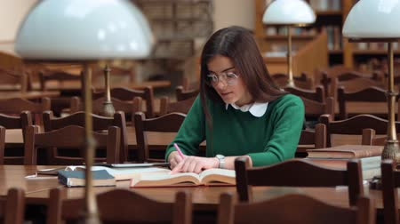 ansiklopedi : Smart young woman in glasses taking notes while revising for exam, wearing smart white blouse and green sweater, indoor shot in old university library Stok Video