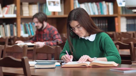 livros didáticos : Intelligent female student taking notes while preparing for exam, using tablet to check the data during revision, wearing smart white blouse and green sweater, indoor shot at brown desk