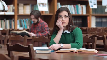 livros didáticos : Pretty young woman have thinking pause as reading book, wearing pristine white blouse and green sweater, indoor shot in library facilities Stock Footage