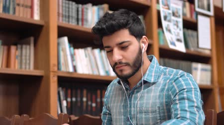 ansiklopedi : Serious student putting on white headphones while reading a book in the library, attractive young man doing home assignment with music