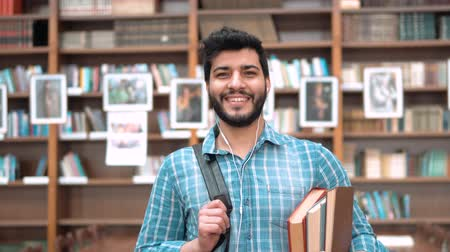 ansiklopedi : Portrait of smart man standing in the library, attractive dark-haired student listening to music in white headphones, holding books and black backpack, wearing blue checked shirt